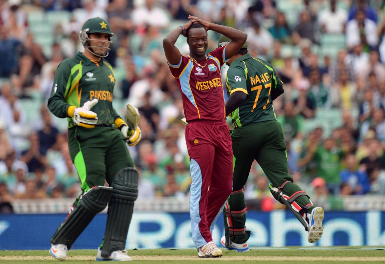 West Indies' Kemar Roach (centre) reacts as Pakistan's Misbah-ul-Haq (left) and Nasir Jamshed (right) put runs on the board during the ICC Champions Trophy match at The Oval, London.