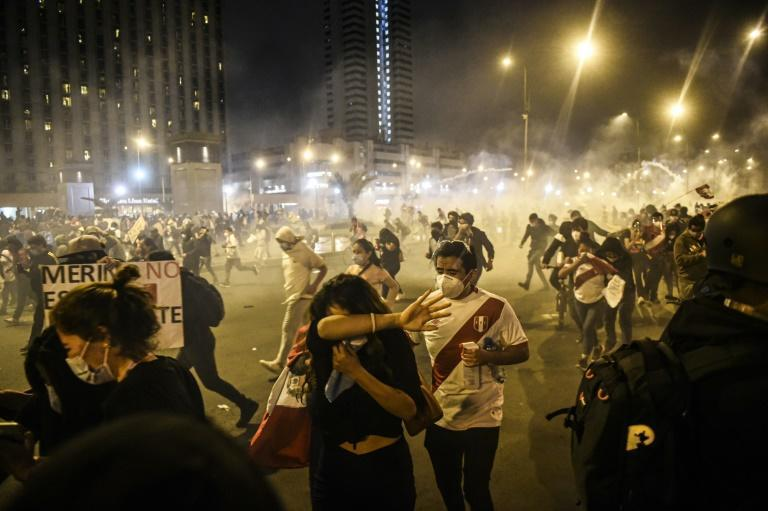 Demonstrators flee tear gas during a protest against the new government of Peru's interim President Manuel Merino on November 12, 2020