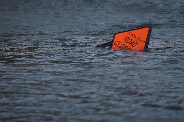 <p>A 'road closed' sign is seen submerged in floodwater during Storm Ophelia in Galway, Ireland, Oct.16, 2017. (Photo: Clodagh Kilcoyne/Reuters) </p>