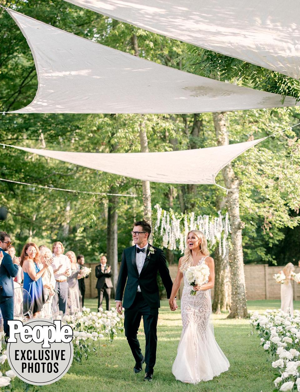 """<p>Following their wedding ceremony between two trees, the newlyweds walked back down the floral-lined aisle covered by sunshades that planner Josiah Carr developed with <a href=""""https://www.tneventdesigns.com/"""" rel=""""nofollow noopener"""" target=""""_blank"""" data-ylk=""""slk:TN Event Designs"""" class=""""link rapid-noclick-resp"""">TN Event Designs</a>.</p>"""