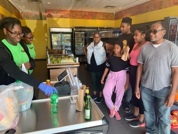 Edmonton pastor Leon Bogle (front right) and his family pick up groceries at Eat Jamaican on Wednesday, Aug. 17. (Thandiwe Konguavi/CBC - image credit)