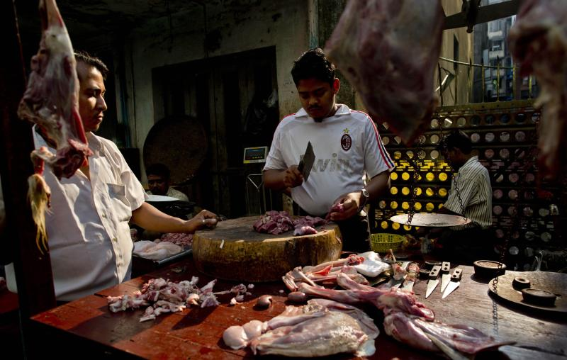 An Indian origin Myanmar Muslim man chops meet at a street market in Yangon, Myanmar, Tuesday, March 26, 2013. Myanmar's government warned Monday that religious violence could threaten democratic reforms after anti-Muslim mobs rampaged through three more towns in the country's predominantly Buddhist heartland. The mobs destroyed mosques and burned dozens of homes over the weekend despite attempts by the government to stem the nation's latest outbreak of sectarian violence. (AP Photo/Gemunu Amarasinghe)