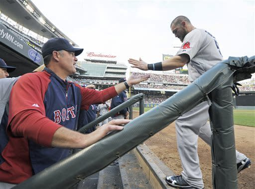 Boston Red Sox manager John Farrell, left, congratulates Jonny Gomes after he scored in the third inning on a single by David Ortiz off Minnesota Twins starting pitcher Scott Diamond in a baseball game, Saturday, May 18, 2013, in Minneapolis. (AP Photo/Jim Mone)