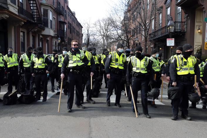 Boston police officers stand in a street in the Beacon Hill neighborhood near the Statehouse, Sunday, Jan. 17, 2021, in Boston. (AP Photo/Michael Dwyer)