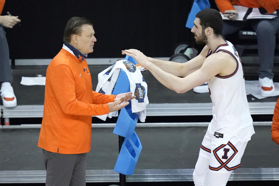 Illinois 's Giorgi Bezhanishvili, right, celebrates with head coach Brad Underwood during the second half of a first round NCAA college basketball tournament game against Drexel Friday, March 19, 2021, at the Indiana Farmers Coliseum in Indianapolis. Illinois won 78-49. (AP Photo/Charles Rex Arbogast)