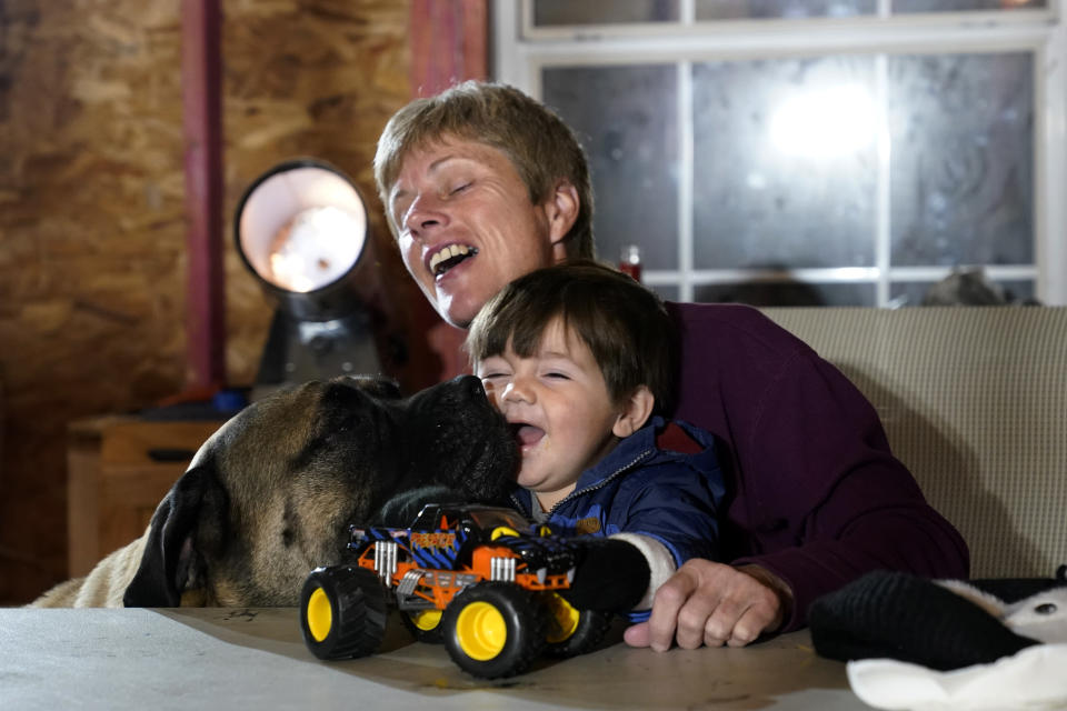 Mary Ann Unson laughs as a family dog licks the face of her great nephew Ricky Trahan III, 1, as one of the family dogs Stella licks his face, on Christmas Eve inside her gutted home, in the aftermath of Hurricane Laura and Hurricane Delta, in Lake Charles, La., Thursday, Dec. 24, 2020. The extended family is living in tents and campers on the property, having all lost their homes to the storms. (AP Photo/Gerald Herbert)