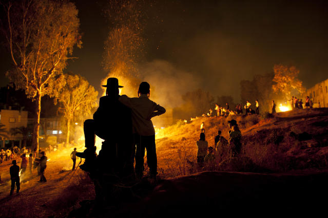 <p>Ultra-Orthodox Jews stand next to bonfires during Lag Ba'Omer celebrations to commemorate the end of a plague said to have decimated Jews in Roman times, in Bnei Brak, Israel, May 9, 2012. (Photo: Oded Balilty/AP) </p>