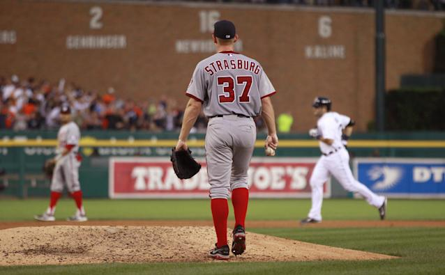 Washington Nationals starting pitcher Stephen Strasburg walks back to the mound as Detroit Tigers' Alex Avila, background, rounds the bases after hitting a grand slam during the sixth inning of a baseball game in Detroit, Tuesday, July 30, 2013. (AP Photo/Carlos Osorio)