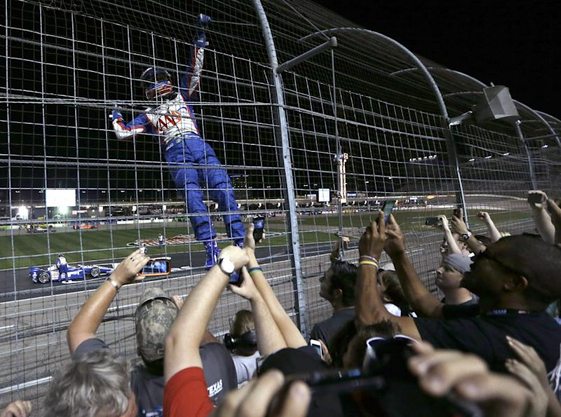 Helio Castroneves, of Brazil, climes the fence after he won the IndyCar auto race Saturday, June 8, 2013, at Texas Motor Speedway in Fort Worth, Texas. (AP Photo/Tim Sharp)