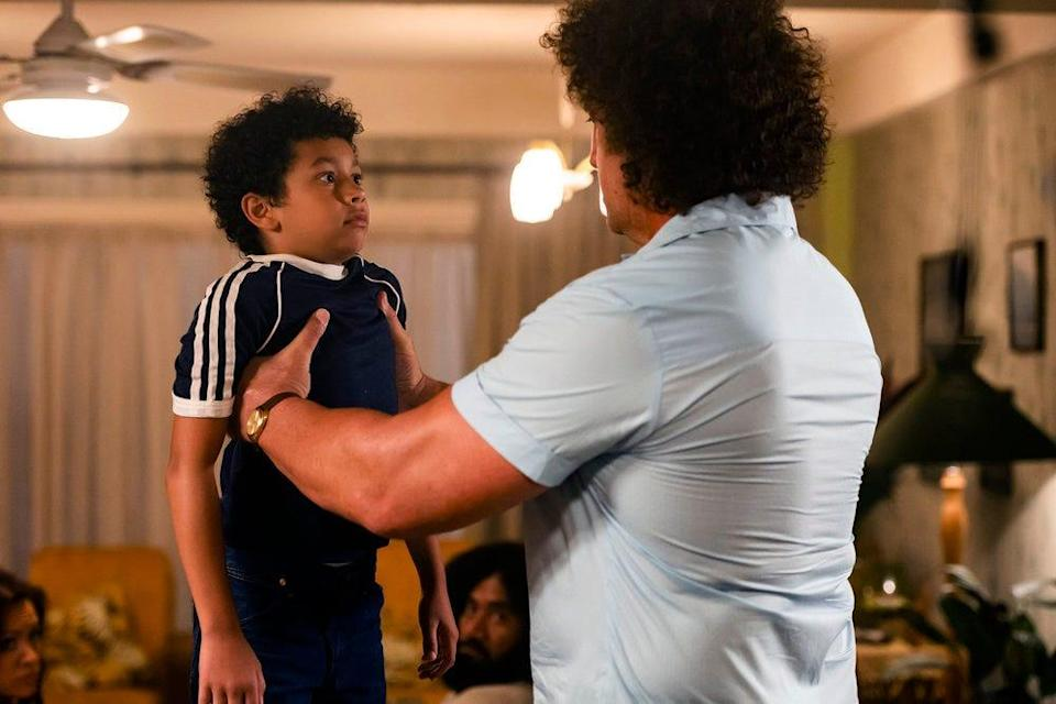 """Andre the Giant (Matthew Willig) lifts a young Dwayne Johnson (Adrian Groulx) in the debut episode of """"Young Rock."""""""