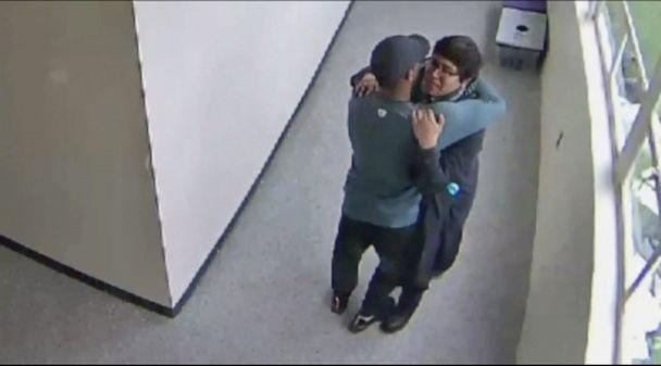 PHOTO: A still from security video shows Parkrose High School coach Keanon Lowe hugging a student who brought a shotgun to school. (KATU)