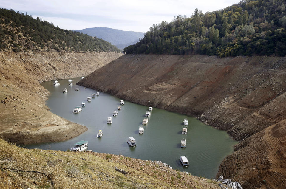 FILE - In this Oct. 30, 2014, file photo, houseboats float in the drought-lowered waters of Oroville Lake near Oroville, Calif. Rainstorms grew more erratic and droughts much longer across most of the U.S. West over the past half-century as climate change warmed the planet, according to a sweeping government study released, Tuesday, April 6, 2021, that concludes the situation in the region is worsening.(AP Photo/Rich Pedroncelli, File)