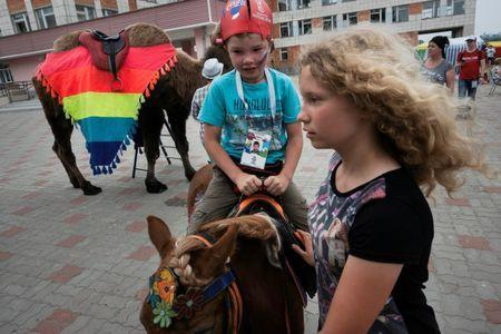 A young soccer fan rides a pony in Bor, Nizhny Novgorod, Russia July 1, 2018. REUTERS/Damir Sagolj