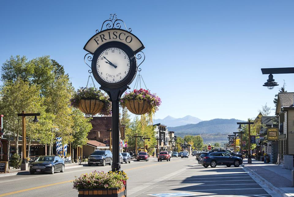 Clock on main street with mountains in the background