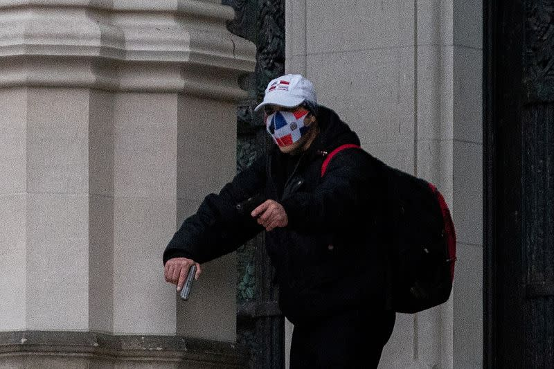 A man wearing a protective mask points his guns outside the Cathedral Church of St. John the Divine in Manhattan