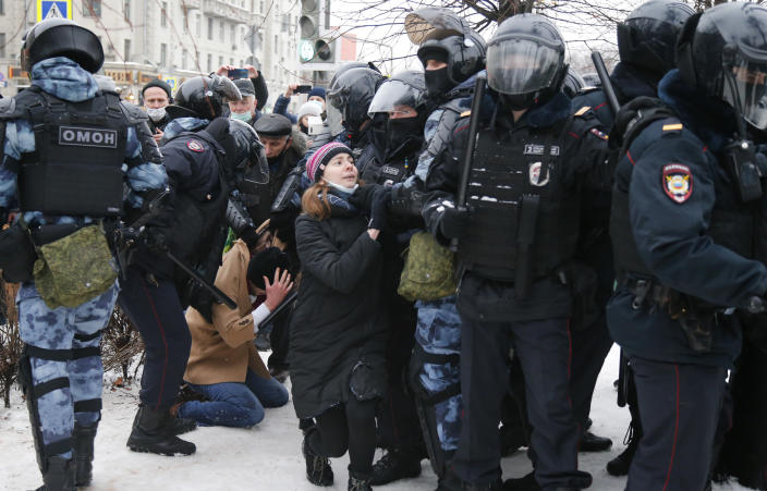 FILE - In this Jan. 23, 2021, file photo, police detain a man as another policeman stops a young woman, center, during a protest against the jailing of opposition leader Alexei Navalny in Moscow, Russia. Allies of Navalny are calling for new protests next weekend to demand his release, following a wave of demonstrations across the country that brought out tens of thousands in a defiant challenge to President Vladimir Putin. (AP Photo/Alexander Zemlianichenko, File)