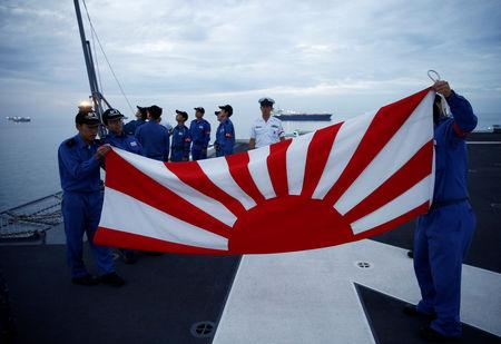 Sailors fold the Japanese naval ensign after a flag lowering ceremony on the deck of Japanese helicopter carrier Kaga anchored near Jakarta Port ahead of its departure for naval drills in the Indian Ocean, Indonesia September 21, 2018. Picture taken on September 21, 2018.  REUTERS/Kim Kyung-Hoon