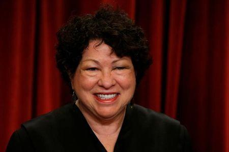 Sotomayor participates in taking a new family photo with her fellow justices at the Supreme Court building in Washington