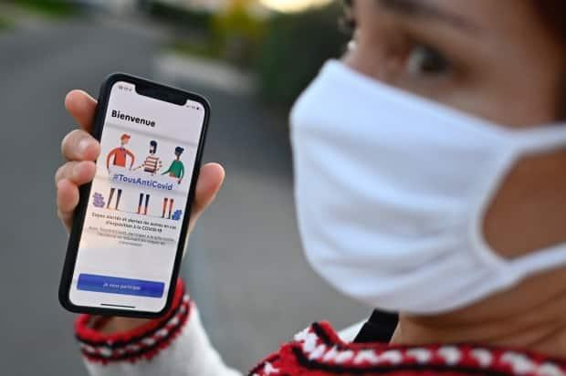 A woman wearing a face mask holds a smartphone showing the Stop COVID contact tracing app in Rennes, western France, last October. Manual contact tracing is a mainstay of public health efforts to control coronavirus epidemics.  (Damien Meyer/AFP/Getty - image credit)