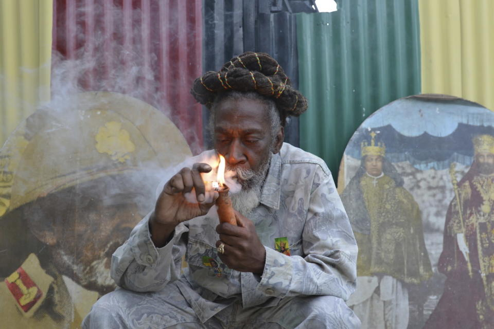 "FILE - In this Aug. 28, 2014 file photo, legalization advocate and reggae legend Bunny Wailer smokes a pipe stuffed with marijuana during a ""reasoning"" session in a yard in Kingston, Jamaica. Wailer, a reggae luminary who was the last surviving original member of the legendary group The Wailers, died on Tuesday, March 2, 2021, in his native Jamaica, according to his manager. He was 73. (AP Photo/David McFadden, File)"