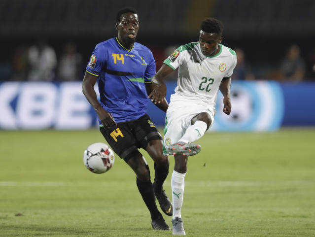 Senegal's Moussa Wague, right, passes the ball by Tanzania's Jhon Raphael Bocco during the African Cup of Nations group C soccer match between Senegal and Tanzania at 30 June Stadium in Cairo, Egypt, Sunday, June 23, 2019. (AP Photo/Hassan Ammar)