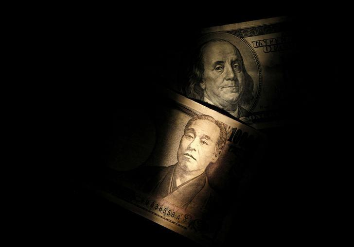Light is cast on U.S. one-hundred dollar bill next to Japanese 10,000 yen note