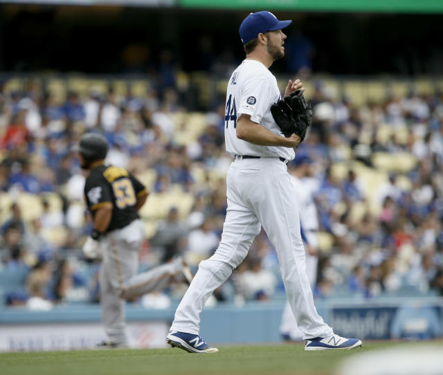 Los Angeles Dodgers starting pitcher Rich Hill, right, looks away as Pittsburgh Pirates' Melky Cabrera, back left, runs the bases after a hitting two-run home run during the second inning of a baseball game in Los Angeles, Sunday, April 28, 2019. (AP Photo/Alex Gallardo)