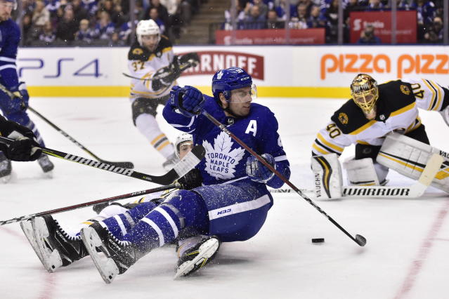 Toronto Maple Leafs center John Tavares (91) manages to get a shot on Boston Bruins goaltender Tuukka Rask (40) after being checked to the ice during the second period of an NHL hockey game, Saturday, Jan. 12, 2019 in Toronto. (Frank Gunn/The Canadian Press via AP)