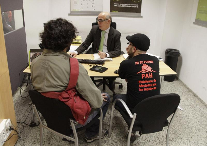 Activists of the Mortgage Victims Platform negotiate with an employee as they occupy a branch of nationalized lender Bankia to protest against home evictions and what they call abusive clauses in mortgage contracts in central Valencia