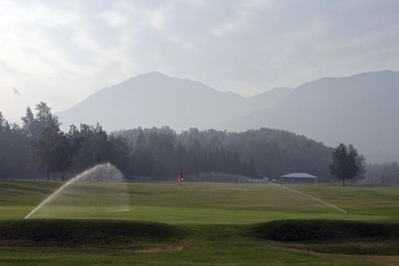 A smoky haze from a wildfire on Alaska's Kenai Peninsula obscures the Chugach Mountains 60 miles (100 km) away in Anchorage, Alaska, on Tuesday, June 25, 2019, as seen from the Moose Run Golf Course. (AP Photo/Mark Thiessen)