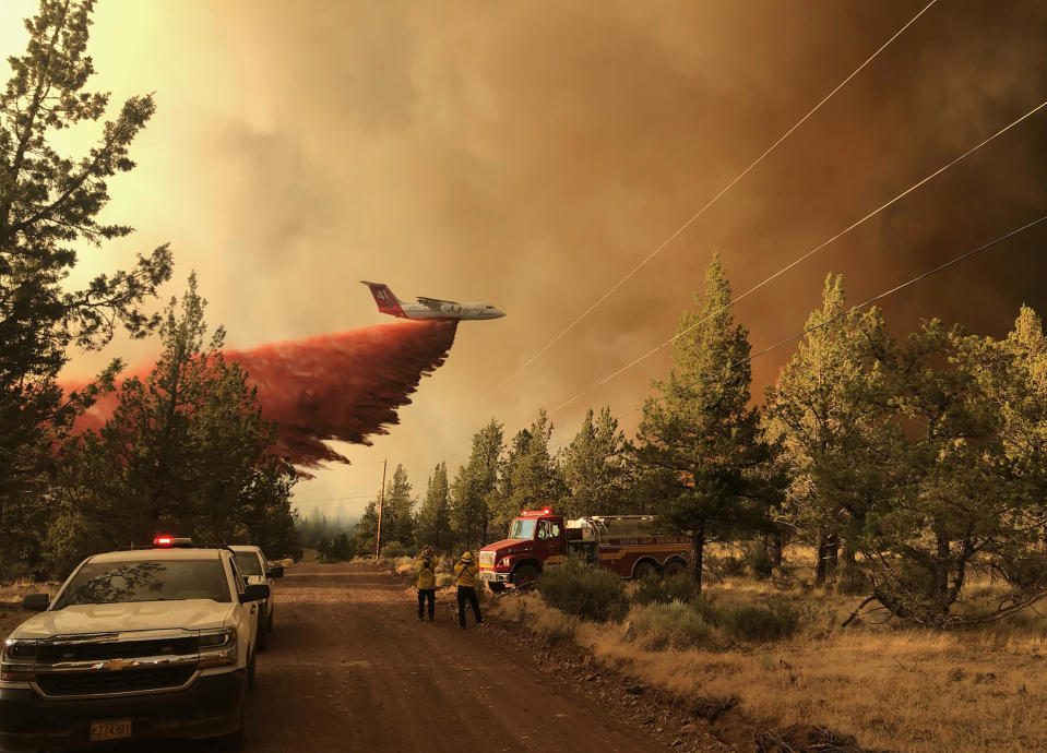 This photo provided by the Oregon Department of Forestry shows a firefighting tanker making a retardant drop over the Grandview Fire near Sisters, Ore., Sunday, July 11, 2021. The wildfire doubled in size to 6.2 square miles (16 square kilometers) Monday, forcing evacuations in the area, while the state's biggest fire continued to burn out of control, with containment not expected until November. (Oregon Department of Forestry via AP)