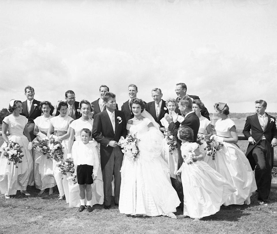 """<p>The fun, casual air of John F. Kennedy and Jacqueline Kennedy surrounded by their groomsmen and bridesmaids on their wedding day in Newport, Rhode Island will almost make you forget they're American royalty. Jackie's boatneck wedding gown was designed by New York City dressmaker, <a href=""""https://www.elle.com/fashion/a29019843/jackie-kennedy-wedding-dress-designer-ann-lowe/"""" rel=""""nofollow noopener"""" target=""""_blank"""" data-ylk=""""slk:Ann Lowe"""" class=""""link rapid-noclick-resp"""">Ann Lowe</a>.</p>"""