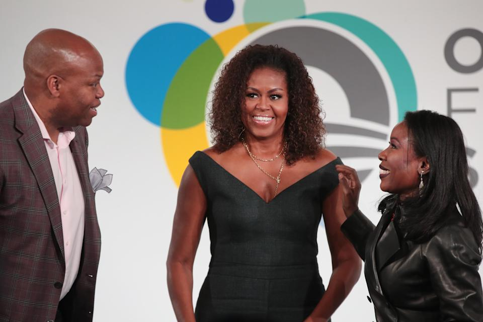"""CHICAGO, ILLINOIS - OCTOBER 29: Former first lady Michelle Obama (C), her brother Craig Robinson, and journalist Isabel Wilkerson speak to guests at the Obama Foundation Summit at Illinois Institute of Technology on October 29, 2019 in Chicago, Illinois. The Summit is an annual event hosted by the Obama Foundation. The 2019 theme is """"Places Reveal Our Purpose"""". (Photo by Scott Olson/Getty Images)"""
