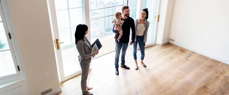 An agent shows a young family a house for sale.