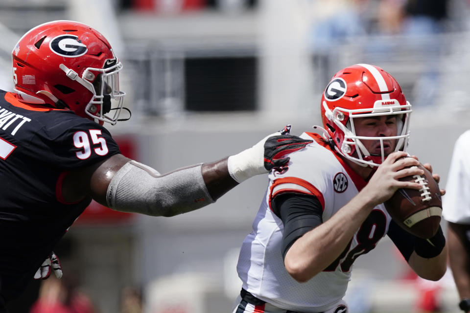 Georgia quarterback JT Daniels (18) is stopped by defensive tackle Devonte Wyatt (95) during their spring NCAA college football game, Saturday, April 17, 2021, in Athens, Ga. (AP Photo/John Bazemore)