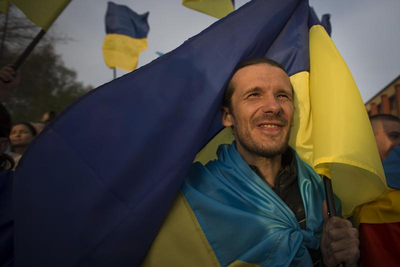 A man holds a Ukrainian national flag during a rally in support of a united Ukraine in Donetsk, Ukraine, Thursday, April 17, 2014. Defense Secretary Chuck Hagel says the U.S. will send nonlethal assistance to Ukraine's military in light of what he called Russia's ongoing destabilizing actions there. (AP Photo/Alexander Zemlianichenko)