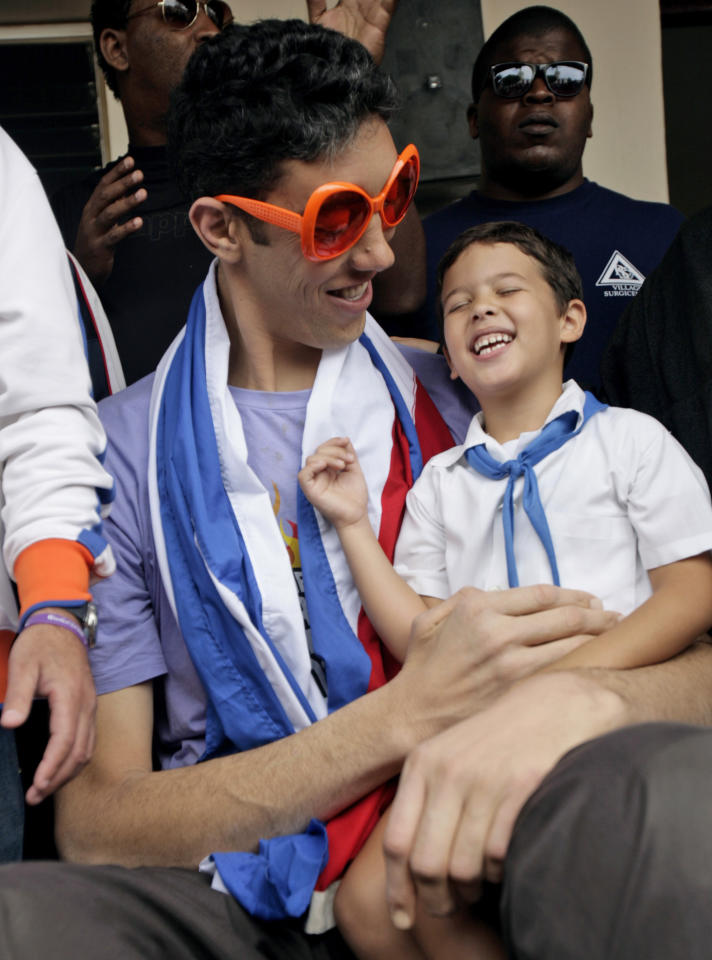 Sultan Kosen, left, of Turkey, who according to the Guinness World Record Association is the world's tallest man, jokes with a student during a visit to the Cesareo Fernandez school in Havana, Cuba, Monday, March 14, 2011. Kosen, 28, is part of a group of young people visiting Cuba with Cuba Amore Foundation, a solidarity organization.