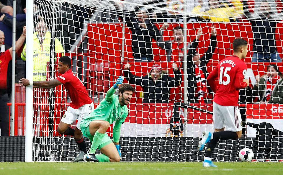 Manchester United's Marcus Rashford (left) scores his side's first goal of the game as Liverpool goalkeeper Alisson (centre) appeals during the Premier League match at Old Trafford, Manchester. (Photo by Martin Rickett/PA Images via Getty Images)