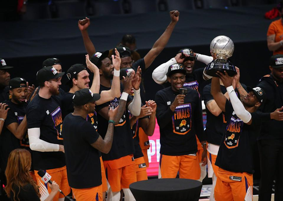 Phoenix Suns guard Chris Paul (3) hoists the Western Conference trophy after beating the LA Clippers in Game 6 at STAPLES Center June 30, 2021.