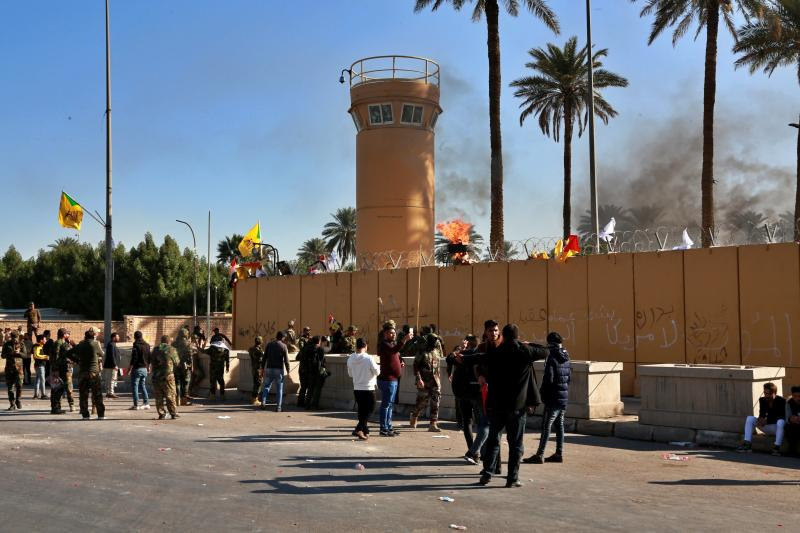 Protesters gather in front of the U.S. embassy compound, in Baghdad, Iraq, Tuesday, Dec. 31, 2019. Dozens of angry Iraqi Shiite militia supporters broke into the U.S. Embassy compound in Baghdad on Tuesday after smashing a main door and setting fire to a reception area, prompting tear gas and sounds of gunfire. (AP Photo/Khalid Mohammed)