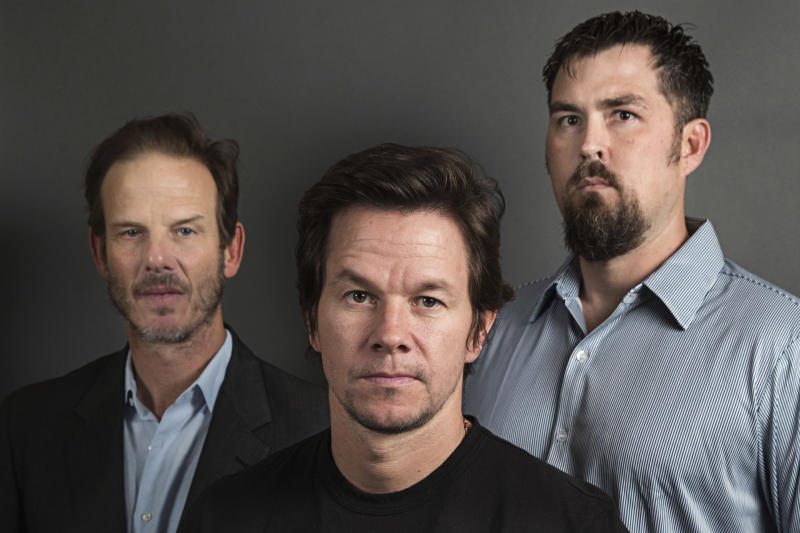 """This Dec. 5, 2013 photo shows director Peter Berg, from left, actor Mark Wahlberg and former Navy SEAL Marcus Luttrell in New York. In the age of the superhero, the movies' most reliable real-life hero has been the Navy SEAL. """"Lone Survivor,"""" starring Mark Wahlberg, is the latest in a string of films, including """"Zero Dark Thirty"""" and """"Act of Valor"""" to honor the Navy's special operations force with as much faithfulness as the filmmakers could muster. (Photo by Victoria Will/Invision/AP)"""