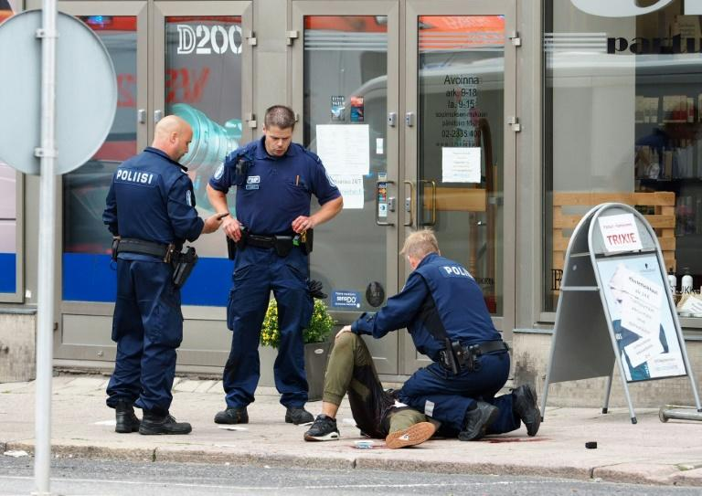 Finnish police officers detain the suspect after he went on the rampage with a knife in the southwestern port city of Turku, killing two and wounding eight