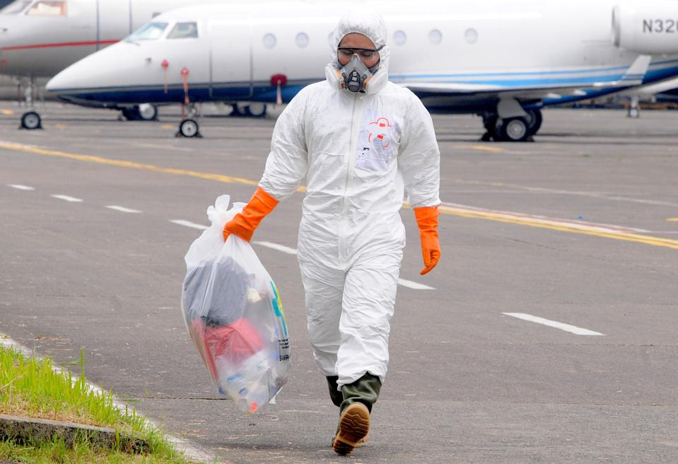 Officers wear hazmat or Corona anti-virus clothes when medical devices arrive from China on the Indonesian air force base Halim Perdanakusuma in Jakarta, Indonesia on March, 23, 2020. When the Corona Virus began to appear (covid-19) anti-virus clothing began to be difficult to obtain by the hospital or someone close to treating the patient because it was only worn once and had to be destroyed. Hazmat clothing is usually used by emergency medical technicians, paramedics, researchers, officers reacting to leakage of hazardous materials, experts who clean contaminated areas, and workers in toxic environments.  (Photo by Dasril Roszandi/NurPhoto via Getty Images)
