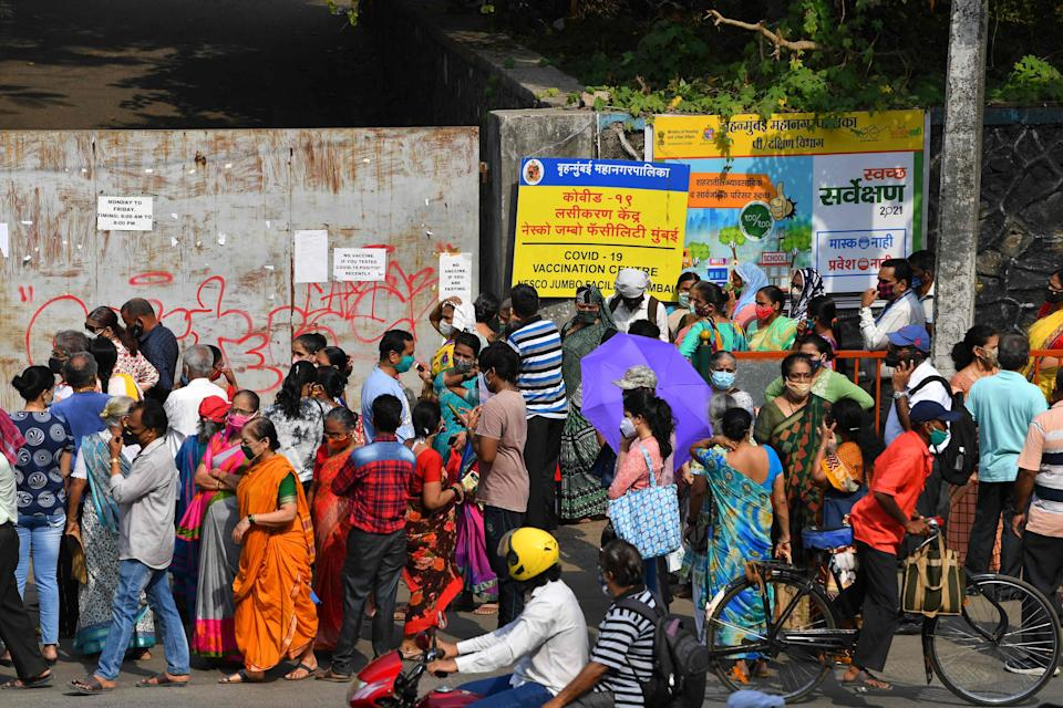 <p>People gather outside an entrance gate of a Covid-19 vaccination centre in Mumbai on 28 April, 2021</p> (AFP via Getty Images)