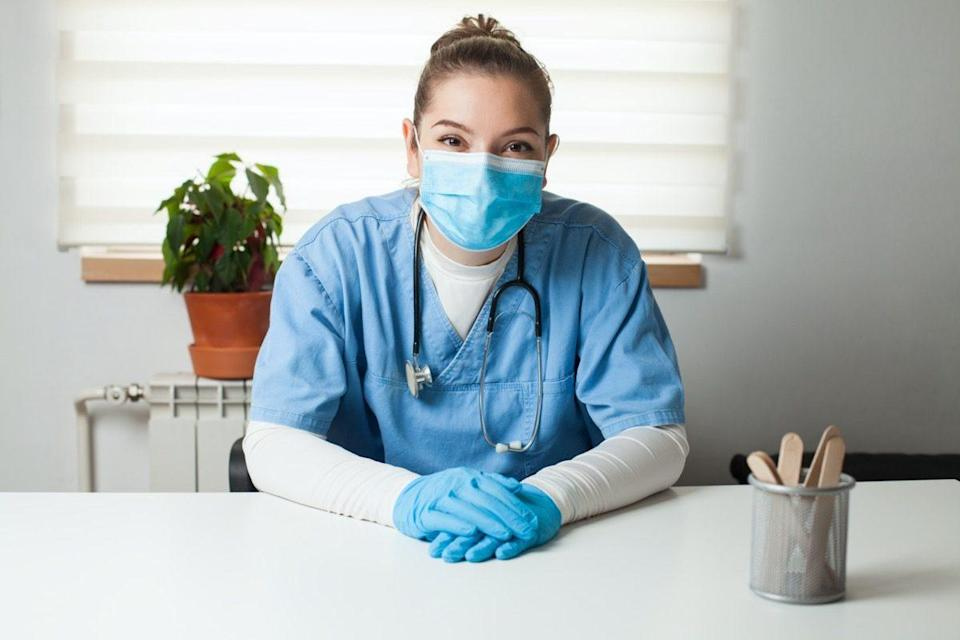 General Practitioner sitting by her desk in office,wearing blue uniform,protective gloves & face mask,virtual tele visit via video call