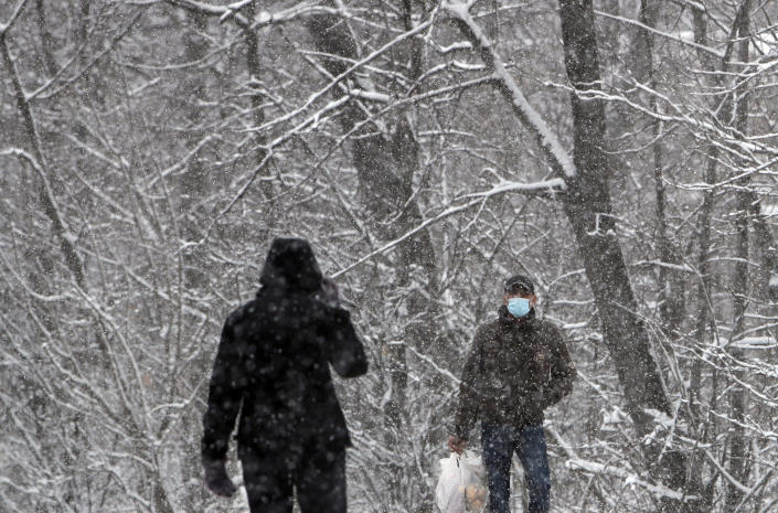 People wearing a face mask to protect against coronavirus walk through a snow covered street in Belgrade, Serbia, Sunday, Jan. 17, 2021. Meteorologists predict sub zero temperatures in Serbia throughout the coming week. (AP Photo/Darko Vojinovic)