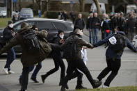 """Participants scuffle at a rally under the slogan """"Free citizens Kassel - basic rights and democracy"""" in Kassel, Germany, Saturday, March 20, 2021. According to police, several thousand people were on the move in the city center and disregarded the instructions of the authorities during the unregistered demonstration against Corona measures. (Swen Pfoertner/dpa via AP)"""