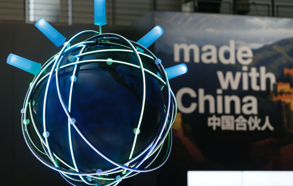 The motto of this year's CeBit trade fair ' Made With China' is seen next to a rotating globe at the IBM booth during the fair in Hanover March 16, 2015. The world's biggest computer and software fair will open to the public from March 16 to 20. (Photo: REUTERS/Morris Mac Matzen)