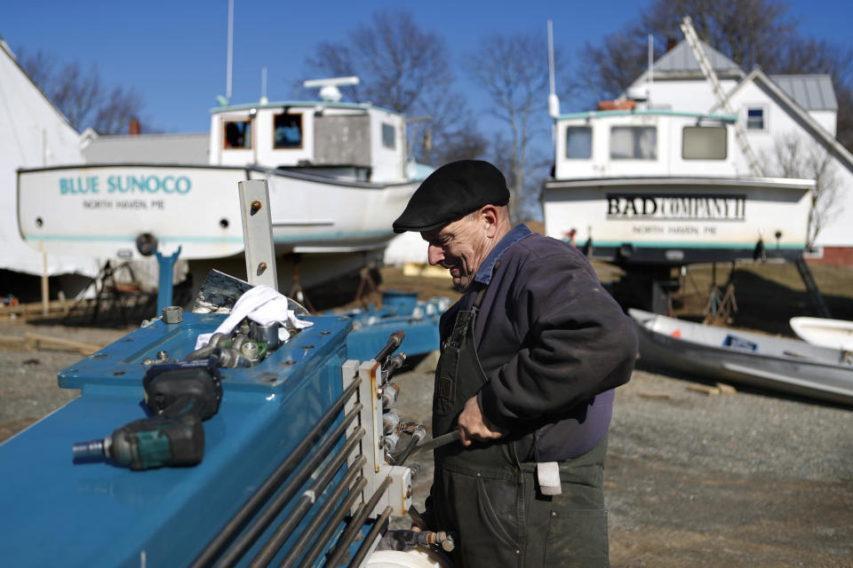 Todd Krause works on a boat lift in Brown's Boat Yard on March 16 on North Haven, Maine, where the Select Board voted to ban visitors and seasonal residents immediately to prevent the spread of the coronavirus to the island in Penobscot Bay. (AP Photo/Robert F. Bukaty)