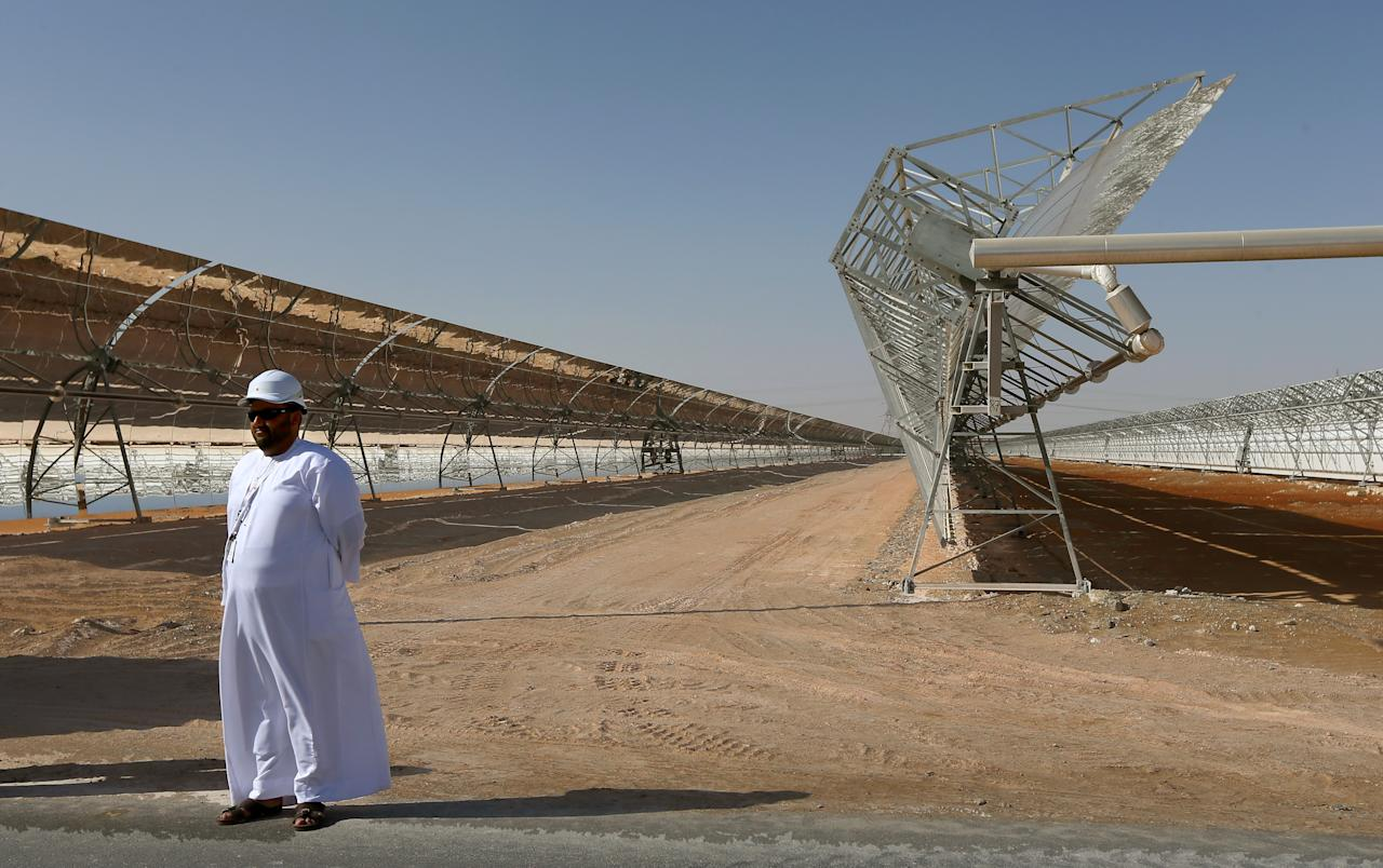 TO GO WITH STORY BY ALI KHALIL An Emarati stands in front of rows of parabolic shaped mirrors at the Shams 1, Concentrated Solar power (CSP) plant, in al-Gharibiyah district on the outskirts of Abu Dhabi, on March 17, 2013 during the inauguration of the facility. Oil-rich Abu Dhabi on Sunday officially opened the world's largest Concentrated Solar Power (CSP) plant, which cost $600 million to build and will provide electricity to 20,000 homes. AFP PHOTO/MARWAN NAAMANI        (Photo credit should read MARWAN NAAMANI/AFP/Getty Images)